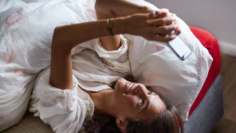 Relaxed young woman using cell phone in bed - stock photo