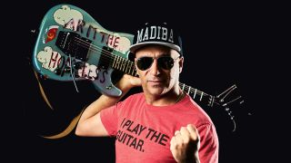 Tom Morello poses with his Arm The Homeless guitar