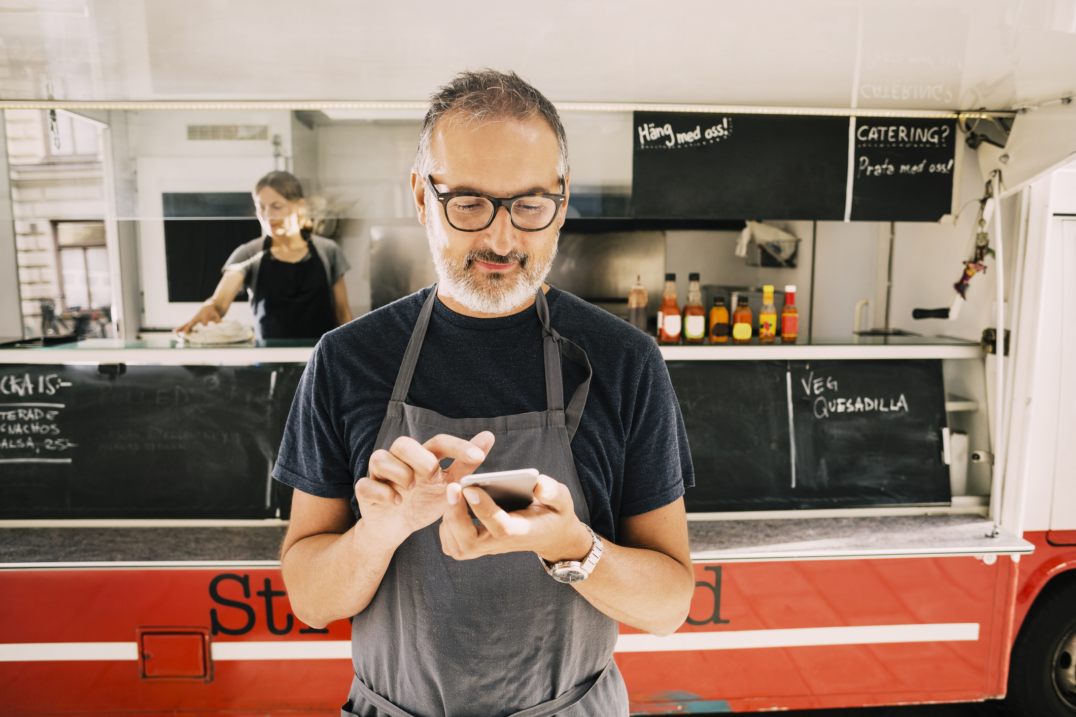 Man uses mobile POS system outside of food truck