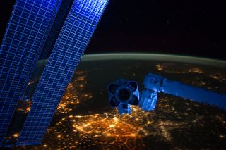 With hardware from the Earth-orbiting International Space Station appearing in the near foreground, a night time European panorama reveals city lights from Belgium and the Netherlands at bottom center. The picture was taken by members of the space station