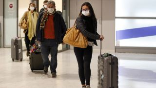 Passengers wear protective masks after landing at Charles De Gaulle Airport on Feb. 10, 2020 in France. Places like airports, bus stops and gas stations are especially risky during the coronavirus pandemic.