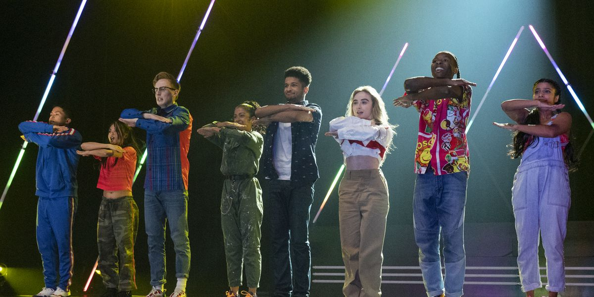 The cast of Work It on a stage practicing.