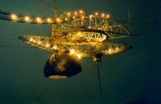 Arecibo Observatory's radio telescope's science platform illuminated at night.