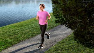 Woman running by a canal wearing a Garmin Forerunner 55 watch
