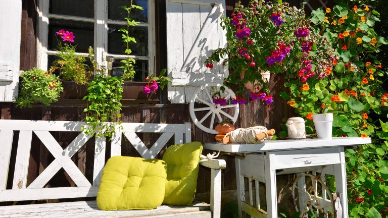 rustic garden ideas: old wooden bench and table in front of a cottage