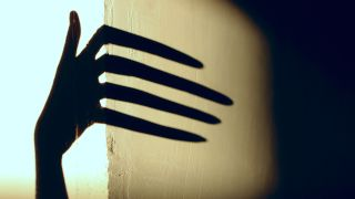A spooky shadow of a hand reaches around a corner.