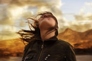 A woman tilts her head back on a windy day.