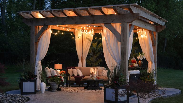Backyard ideas: pergola at dusk with outdoor sofas and lighting