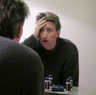 Man in a dark sweater is looking in the mirror of a hotel room with a shocked look on his face.