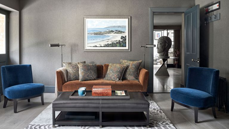 An example of dark living room ideas showing a living room with gray walls and orange and blue sofas