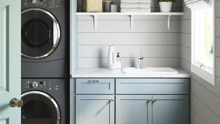 sterling sink in small laundry room with blue cabinets, white worktop, stacked washing machine and dryer