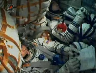 NASA astronaut Dan Burbank and Russian cosmonauts Anton Shkaplerov and Anatoly Ivanishin are pictured inside their Soyuz TMA-22 spacecraft minutes prior to their launch to the International Space Station.