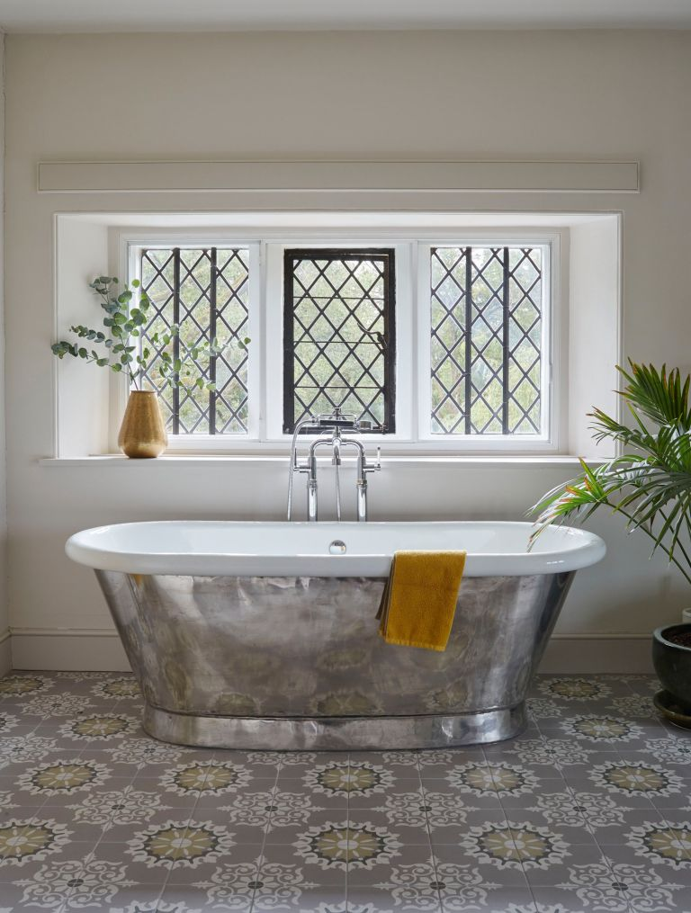 Luxury bathroom with silver bath, ornate tiles and leaded windows