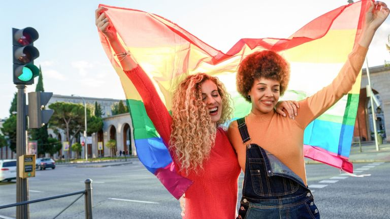 LGBTQ+ ally Lesbian women couple in the city with gay pride rainbow flag - stock photo