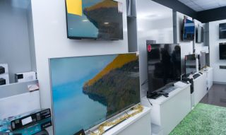 Flatscreen TVs on display in a retail store.