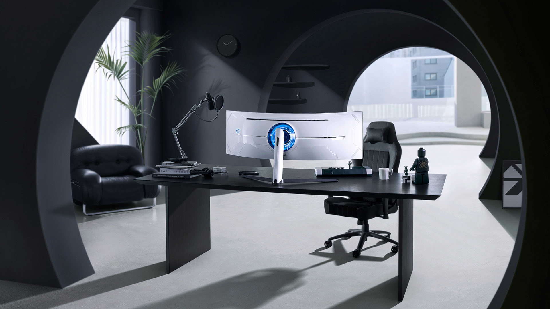 Samsung Odyssey Neo G9 from behind on a fancy desk. Has a blue RGB light on it.