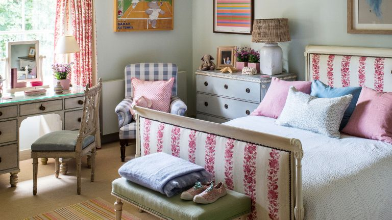 Kids' room ideas in a pale gray-green bedroom with dressing area and pink and white upholstered bed and drapes.