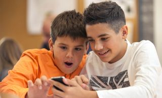 Two boys smile while looking at a cell phone