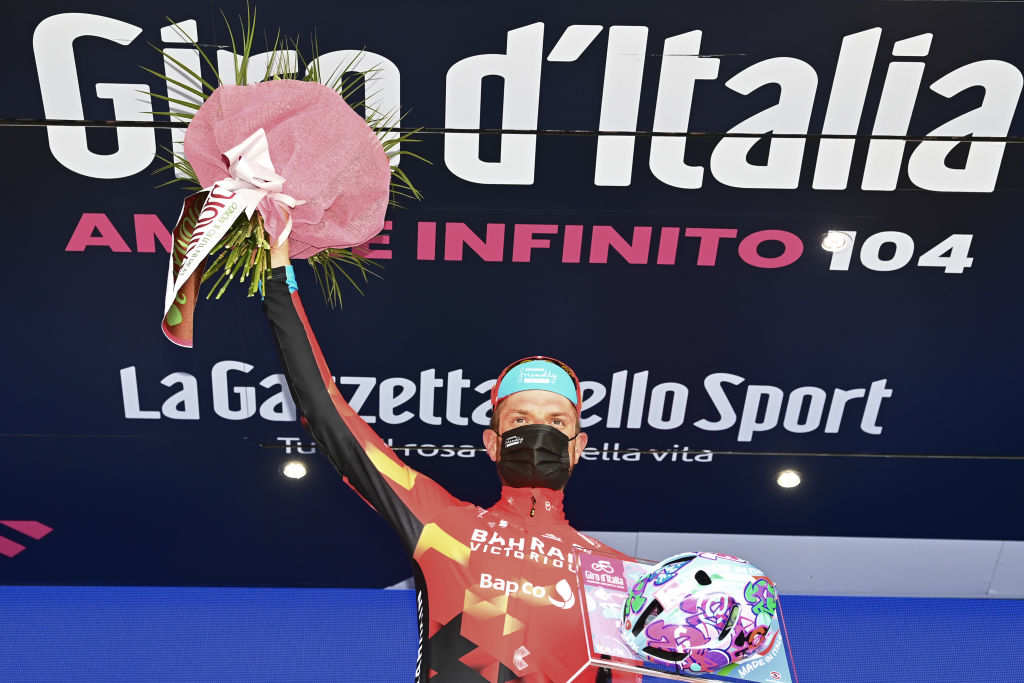 VALLE SPLUGA ALPE MOTTA ITALY MAY 29 Damiano Caruso of Italy and Team Bahrain Victorious celebrates at podium during the 104th Giro dItalia 2021 Stage 20 a 164km stage from Verbania to Valle Spluga Alpe Motta 1727m Kask Utopia Giro Helmet designed by MotoGP artist Aldo Drudi to stage winners The peloton passing through flowery landscape UCIworldtour girodiitalia Giro on May 29 2021 in Valle Spluga Alpe Motta Italy Photo by Stuart FranklinGetty Images