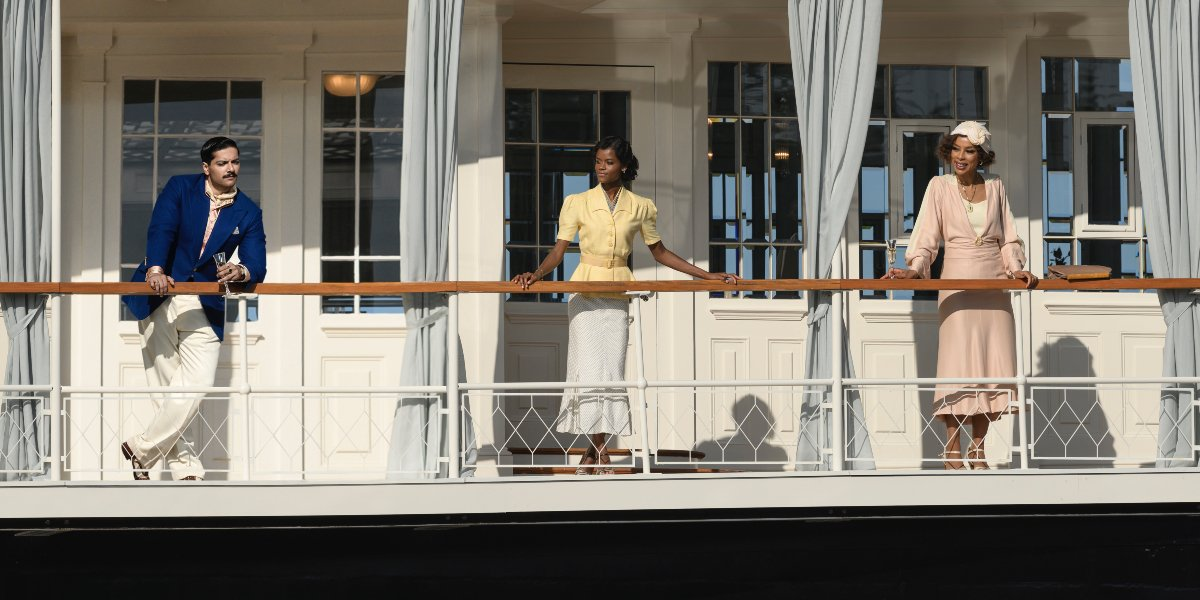 Death on the Nile cast members standing on the deck in the sunlight