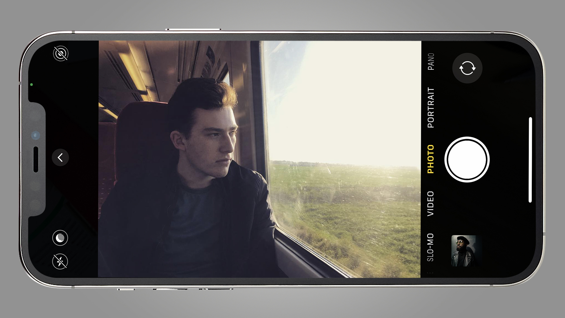 A man looking out of a train window on a phone screen