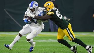 Jamaal Williams #30 of the Detroit Lions is tackled by Krys Barnes #51 of the Green Bay Packers during the second half at Lambeau Field on Sept. 20, 2021 in Green Bay, Wisconsin.