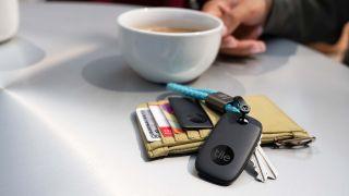 Tile Pro på bord med plånbok och kaffekopp.
