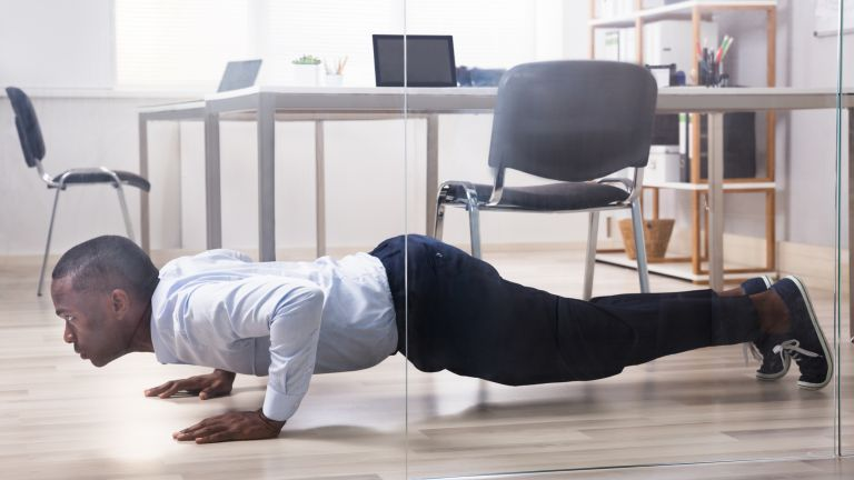 Man doing a push up micro workout in the office