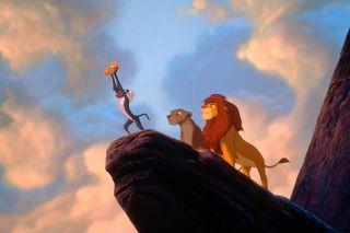 Rafiki holding baby Kiara on Pride Rock as Simba and Nala watch.