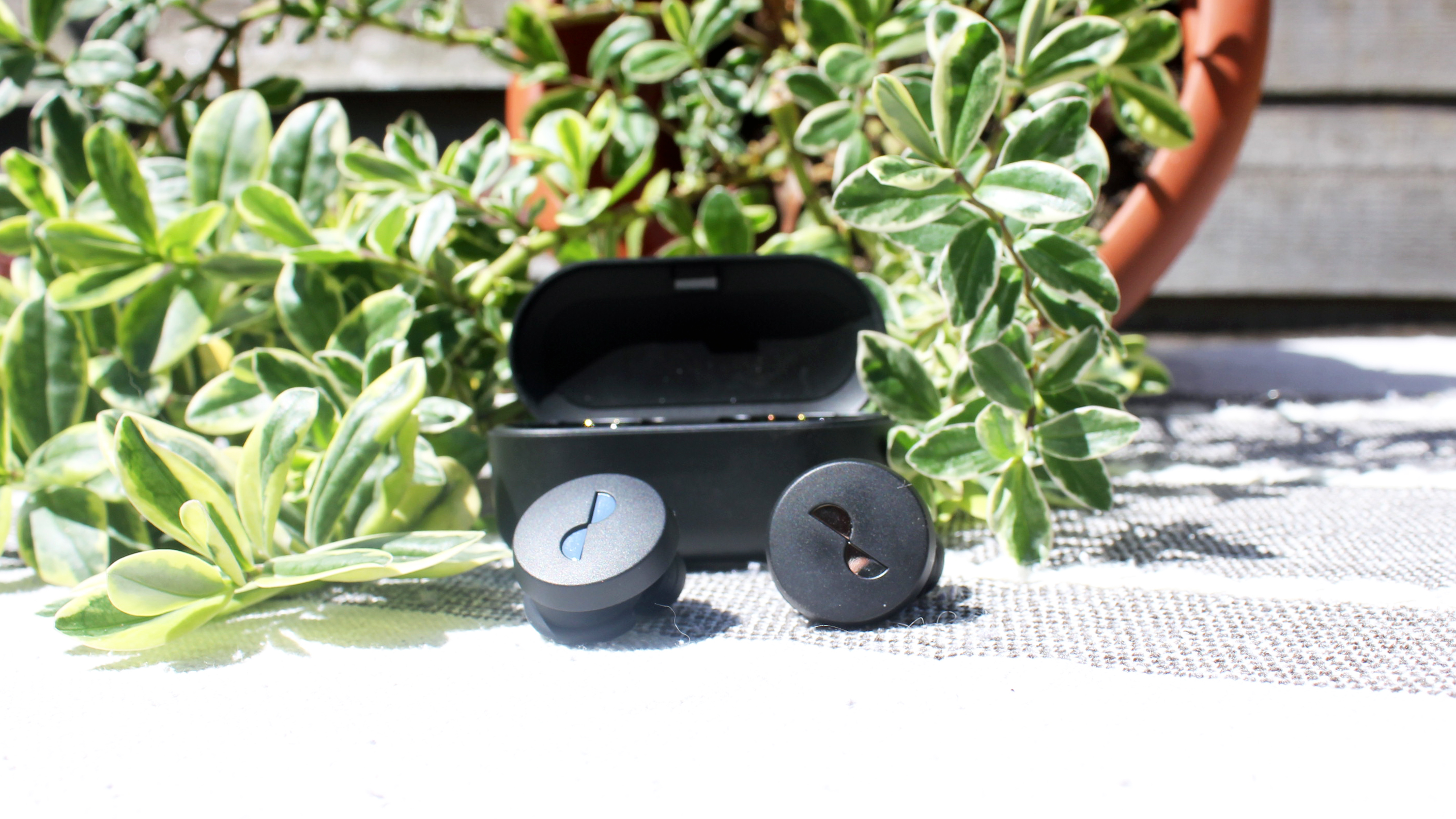 the nuratrue wireless earbuds in front of their charging case
