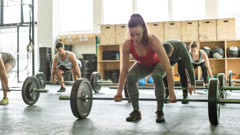 Woman doing deadlifts as part of a crossfit class