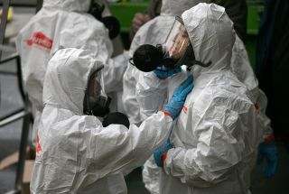 workers put on personal protective equipment before entering the LifeCare facility in Kirkland Washington, where a huge outbreak of COVID-19 occurred.