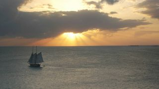 Old fashioned sailing vessel on the sea, with setting sun on the horizon