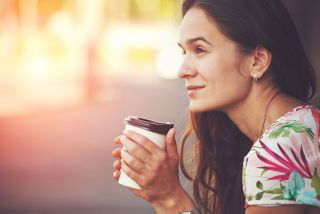 A woman drinks a cup of coffee and looks happy