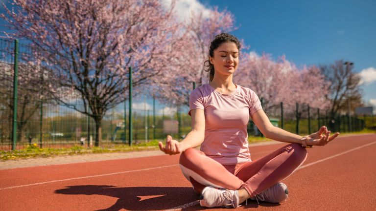 Women sits on an athletic track in a meditative pose