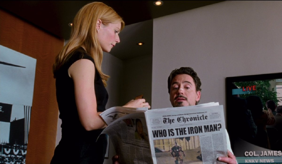 Iron Man Gwyneth Paltrow fixes up Robert Downey Jr as he reads the paper