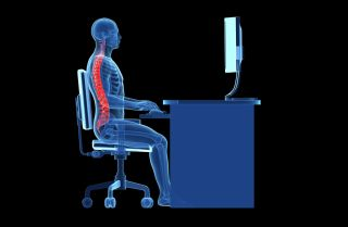 An artist's image shows the form of a human body sitting with proper posture at a desk.