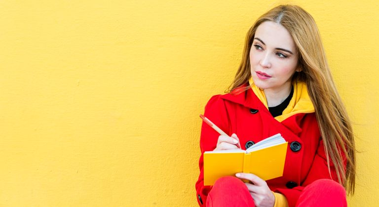 Thoughtful woman wearing a red jacket sitting against a yellow wall while writing notes