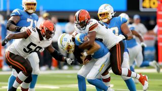 Justin Herbert #10 of the Los Angeles Chargers is sacked by Myles Garrett #95 and Malik McDowell #58 of the Cleveland Browns during the third quarter at SoFi Stadium on Oct. 10, 2021 in Inglewood, California.