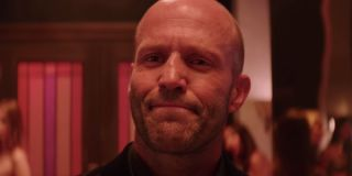 Hobbs and Shaw Deckard Shaw smiling in the middle of a colorful club scene