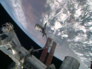An Orbital Sciences-built Cygnus spacecraft is captured by a robotic arm on the International Space Station during docking activities on July 16, 2014. The unmanned Cygnus spacecraft delivered more than 1.5 tons of supplies to the station for NASA.