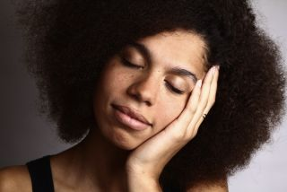 A woman with an afro sleeps.