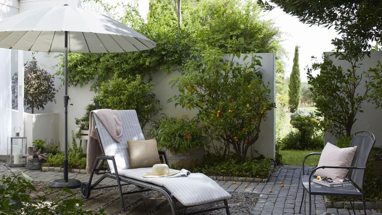 Make a small garden look bigger with the best patio umbrella: garden with sunlounger and patio umbrella by john lewis & partners