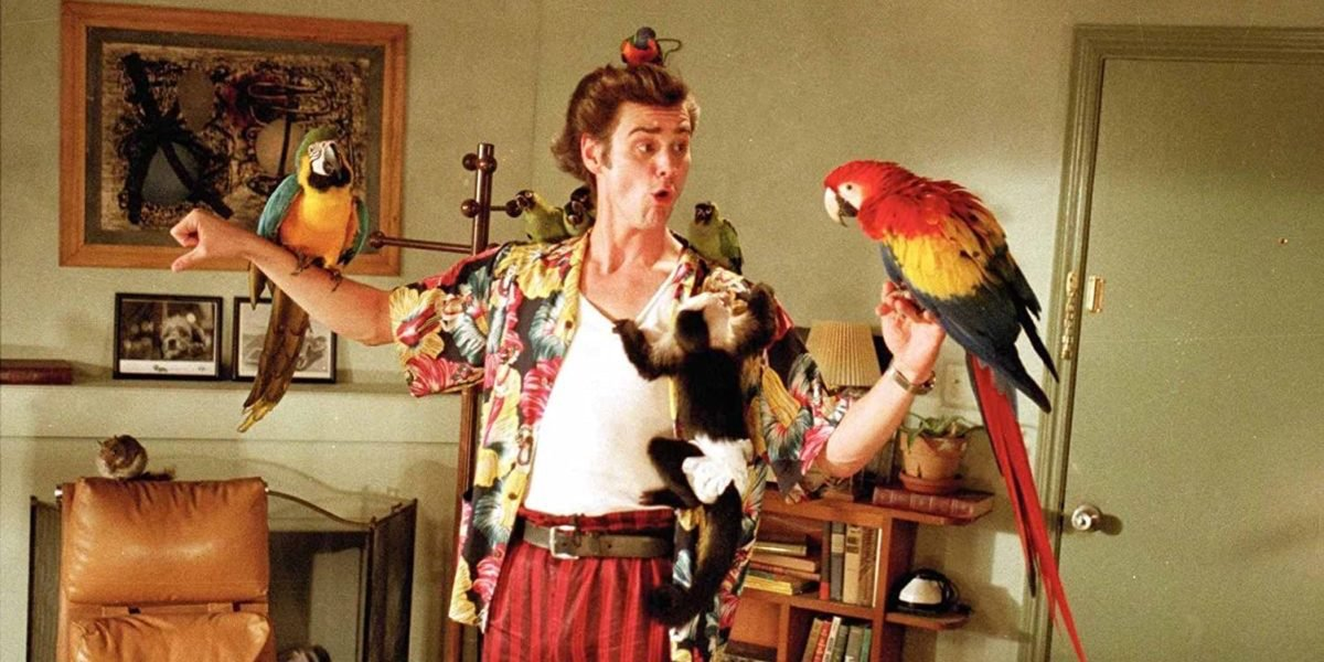 Jim Carrey as Ace Ventura with birds and a monkey on his body