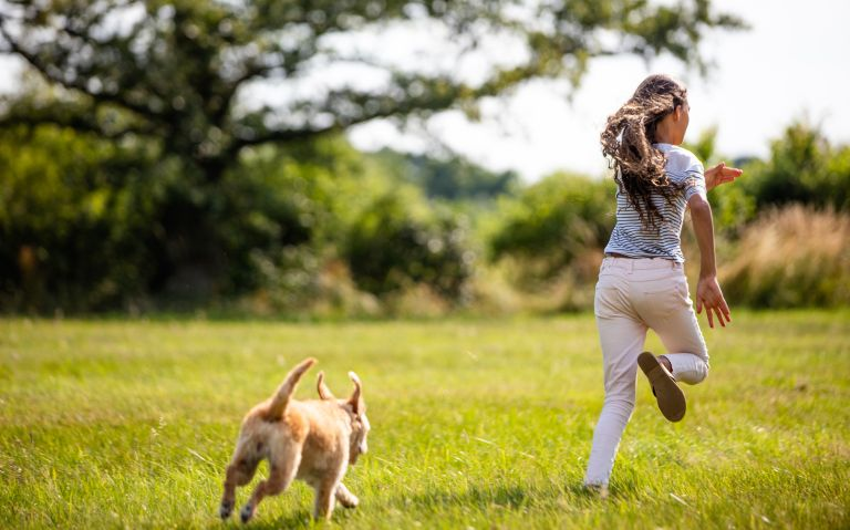 girl and dog running through a field in the countryside