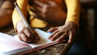 A girl writes in a notebook with her right hand.