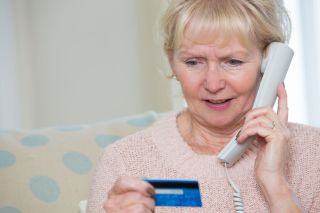 Concerned elderly woman reads payment card while holding phone.