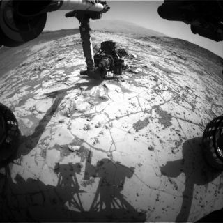 """This photo — taken on Jan. 13, 2015 by one of the Curiosity Mars rover's hazard cameras — shows the rover in position for a mini-drill test on a rock target called """"Mojave."""""""