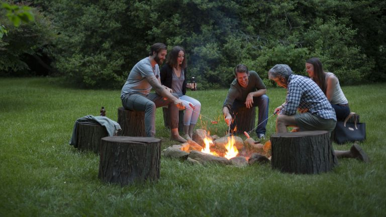 How to build a fire pit: group of adults sitting around a fire pit in a field