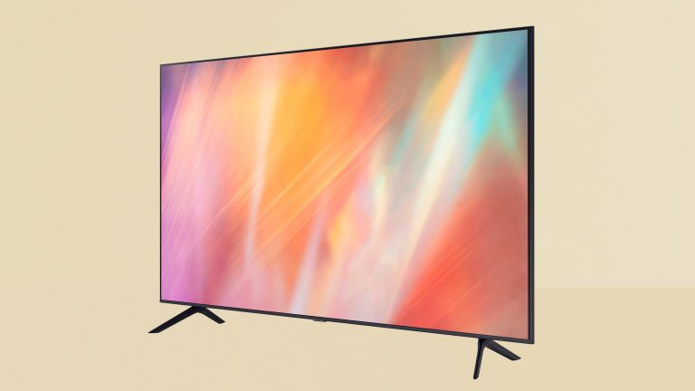 Samsung AU7100 review image showing the TV on a yellow background. The TV has a black frame with two arrow-shaped legs